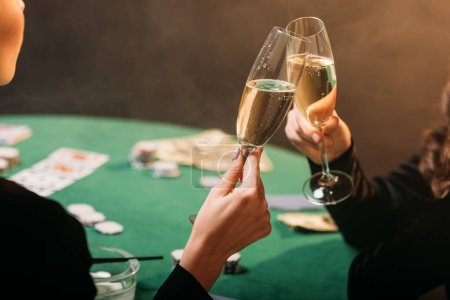 Photo for Cropped image of girls clinking with glasses of champagne at poker table in casino - Royalty Free Image