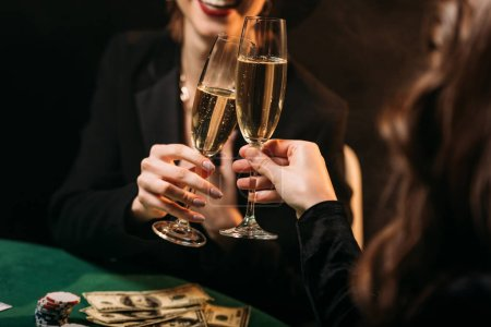 Photo for Cropped image of happy girls clinking with glasses of champagne at poker table in casino - Royalty Free Image