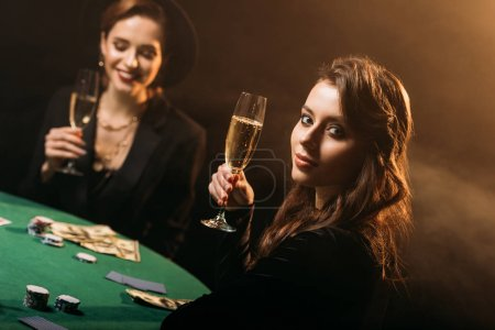 Photo for Attractive girls holding glasses of champagne at poker table in casino - Royalty Free Image