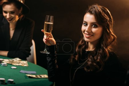 smiling attractive girl holding glass of champagne at poker table in casino and looking at camera