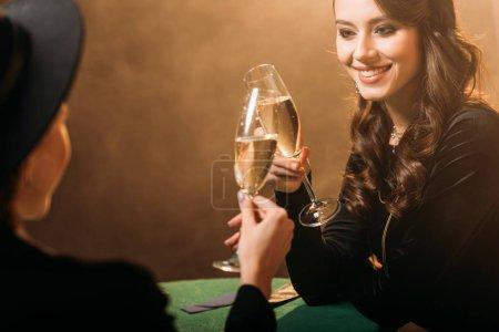 Foto de Sonriendo a las mujeres atractivas que tintinea con copas de champán a la mesa de poker en casino - Imagen libre de derechos