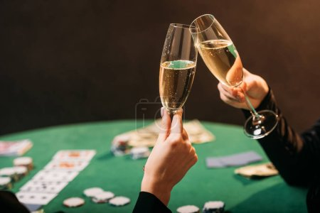 cropped image of women clinking with glasses of champagne at poker table in casino