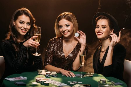 Photo for Smiling attractive girls with glass of champagne, cigarette and poker chips sitting at table in casino - Royalty Free Image