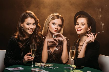 beautiful women with glass of champagne, cigarette and poker chips sitting at table in casino