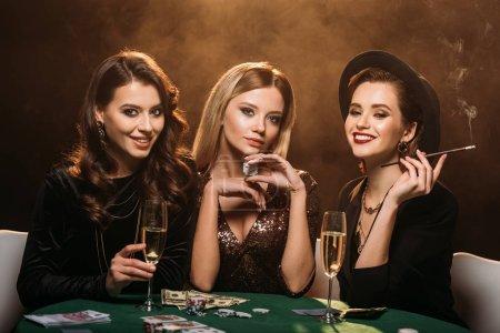 Photo pour Belles femmes avec verre de champagne, de cigarettes et de poker chips assis à table au casino - image libre de droit