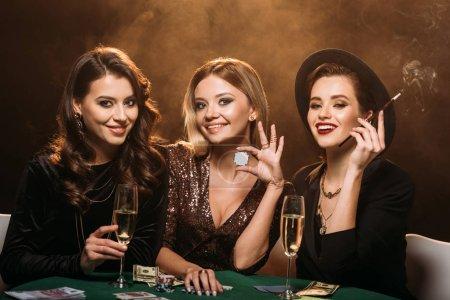 Photo pour Heureux amis attrayants avec verre de champagne, de cigarettes et de poker chips assis à table dans le casino et regardant la caméra - image libre de droit