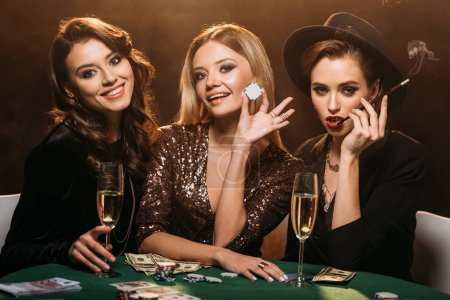 Photo pour Sourire des jolies filles assis à table dans le casino et regardant la caméra - image libre de droit