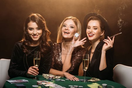 Photo for Laughing attractive girls with glass of champagne, cigarette and poker chips sitting at table in casino - Royalty Free Image