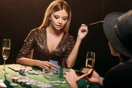 attractive girls smoking cigarettes and playing poker at table in casino