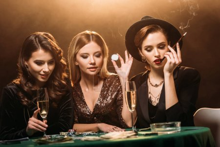 attractive girls with glass of champagne, cigarette and poker chips sitting at table and looking at poker cards in casino