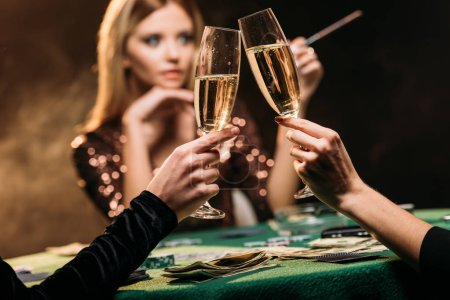 selective focus of attractive girls clinking with glasses of champagne at poker table in casino