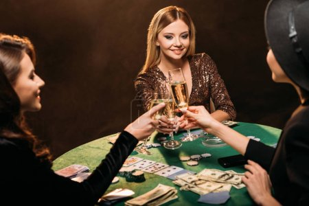 happy attractive girls clinking with glasses of champagne at poker table in casino