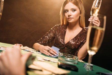 Foto de Chica atractiva con Copa de champán en la mesa de póker en casino y mirando lejos - Imagen libre de derechos