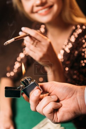Photo for Cropped image of man lighting cigarette to smiling girl at poker table in casino - Royalty Free Image
