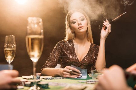 selective focus of attractive girl smoking cigarette at poker table in casino