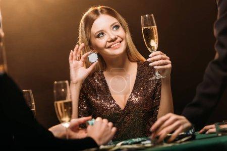 Foto de Hermosa mujer feliz celebración Copa de champagne y poker chip en mesa de casino y mirando hacia arriba - Imagen libre de derechos
