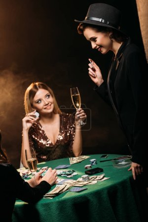 Photo for Smiling attractive girls with glasses of champagne talking at poker table in casino - Royalty Free Image
