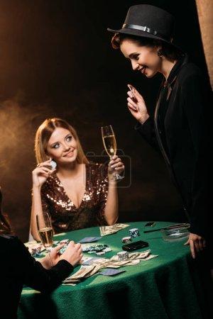 Photo pour Sourire des jolies filles avec verres de champagne, parler à la table de poker au casino - image libre de droit