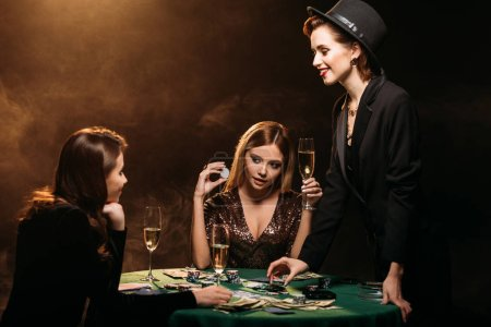 attractive girls with glasses of champagne at poker table in casino