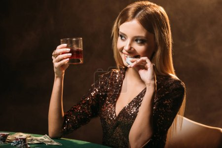 Photo pour Attrayant souriant verre tenue fille de whisky et mordre poker chip à table au casino - image libre de droit
