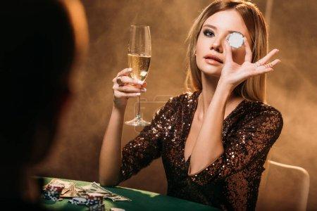 Foto de Chica atractiva celebración de Copa de champán y cubriendo el ojo con el chip de poker en mesa de casino - Imagen libre de derechos