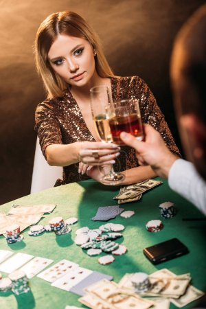 attractive girl and croupier clinking with glasses of alcohol drinks while playing poker at casino