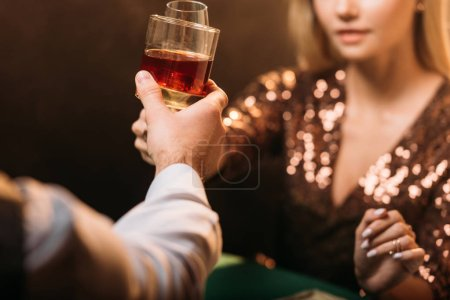 Photo for Cropped image of girl and croupier clinking with glasses of alcohol drinks while playing poker at casino - Royalty Free Image