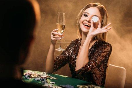 Photo pour Heureuse jolie fille tenant le verre de champagne et couvrant les yeux avec le jeton de poker au casino - image libre de droit