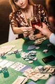 cropped image of girl and croupier clinking with glasses of alcohol drinks while playing poker at casino
