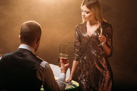 Photo for Attractive girl and croupier holding glasses of alcohol drinks at poker table in casino - Royalty Free Image