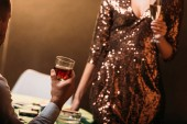 cropped image of girl and croupier holding glasses of alcohol drinks at poker table in casino