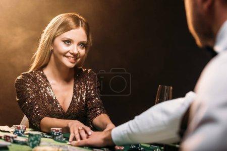 Photo pour Heureuse jolie fille prendre des jetons de poker et en regardant de croupier au casino - image libre de droit
