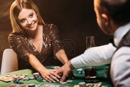 Foto de Chica atractiva sonriente tomando fichas de póker y mirando de croupier en el casino - Imagen libre de derechos