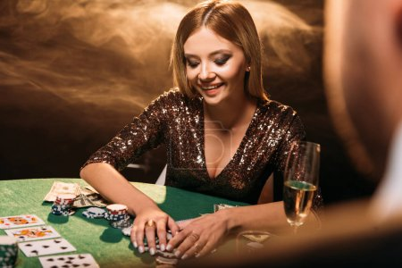 Photo for Smiling beautiful girl taking poker chips and looking down at casino - Royalty Free Image