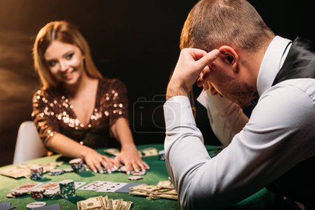 Photo for Smiling attractive girl taking poker chips and looking at sad croupier at casino - Royalty Free Image