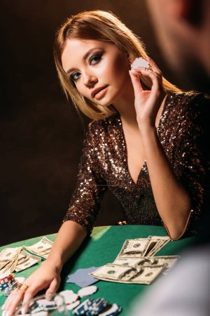attractive girl holding poker chip and looking at croupier at casino