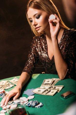Foto de Chica atractiva celebración de fichas de póker y mirando a la mesa en el casino - Imagen libre de derechos