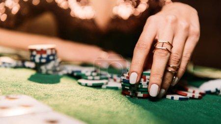Foto de Imagen recortada de niña jugando a poker y tomando fichas en mesa de casino - Imagen libre de derechos