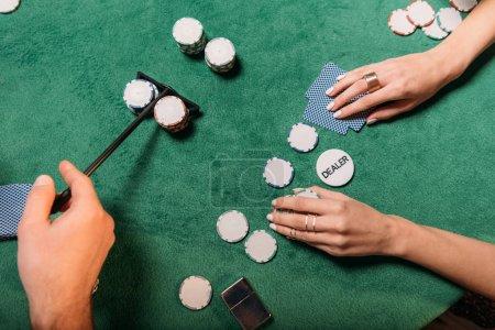 Foto de Imagen recortada de la mujer y el crupier jugar al póquer en la mesa en el casino - Imagen libre de derechos
