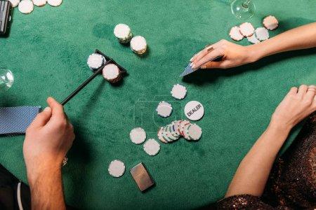 Foto de Imagen recortada de niña y crupier jugar al póquer en la mesa en el casino - Imagen libre de derechos