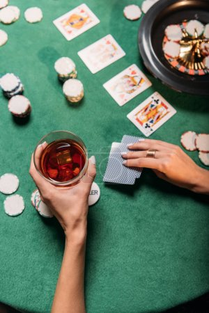 cropped image of girl playing poker and holding glass of whiskey at table in casino