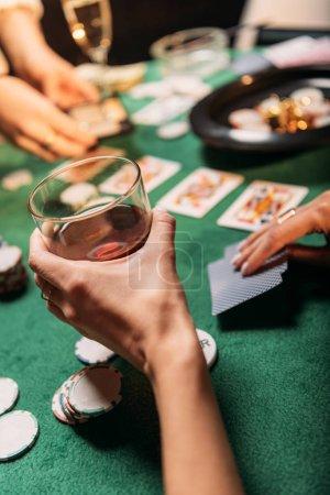 Foto de Imagen recortada de mujer jugando al poker y sosteniendo el vaso de whisky en mesa de casino - Imagen libre de derechos