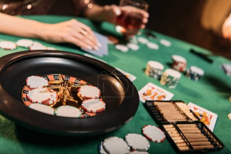 cropped image of girl playing poker at table in casino, roulette and cigars on foreground