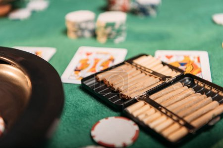 roulette and cigars and poker cards on table in casino