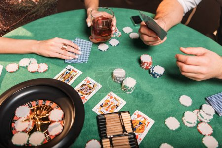 cropped image of girl and croupier playing poker at table in casino
