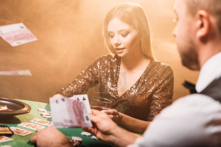 Photo for Attractive girl playing poker with croupier at casino, money falling on table - Royalty Free Image