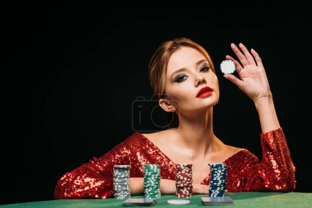 Photo for Attractive girl in red shiny dress leaning on table, holding poker chip and looking at camera isolated on black - Royalty Free Image