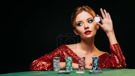 Photo for Attractive girl in red shiny dress leaning on table, holding poker chip and looking away isolated on black - Royalty Free Image