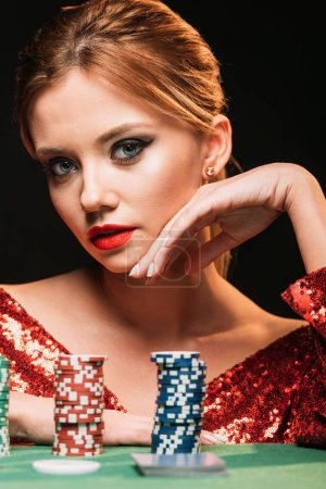 Photo for Portrait of attractive girl in red shiny dress leaning on table with poker chips isolated on black - Royalty Free Image