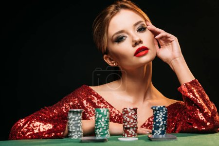 Photo for Beautiful girl in red shiny dress leaning on table with poker chips and looking at camera isolated on black - Royalty Free Image